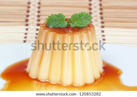 Delicious sweet pudding with caramel and mint leaves on a decorative napkin.