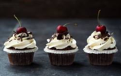 delicious sweet three cupcakes decorated with cream, chocolate and fresh cherry
