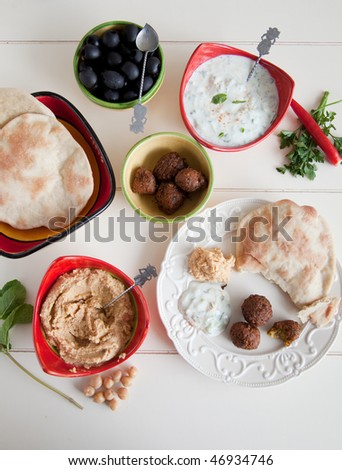 Delicious table filled with snack such as homemade pita, tzatziki, hummus and falafel