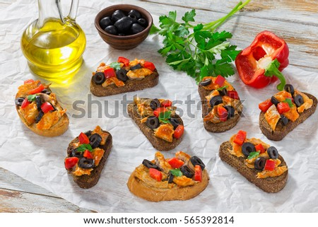 delicious tapas with pieces of mackerel fish, rings of black olives, red bell pepper on white plate on paper, bottle with cooking oil and parsley on wooden background, top view