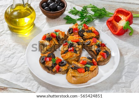 delicious tapas with pieces of mackerel fish, rings of black olives, red bell pepper on white plate on paper, bottle with cooking oil and parsley on wooden background, close-up