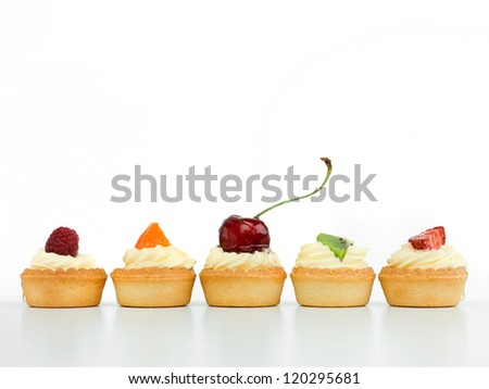 delicious tart arranged in line with raspberry cherries kiwi strawberry apricot white background izolated
