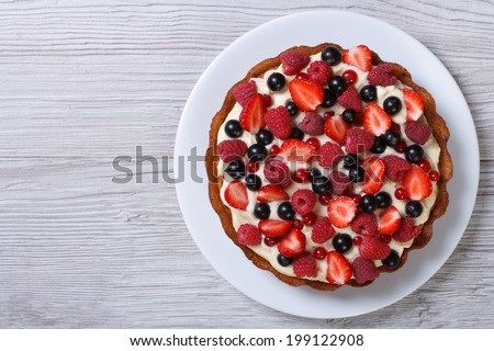 Delicious tart with fresh strawberries, raspberries and currants on the table. top view horizontal  #199122908