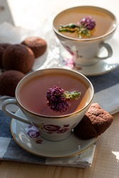 delicious tea with clover in a beautiful white set with pink flowers and a saucer with brown cookies