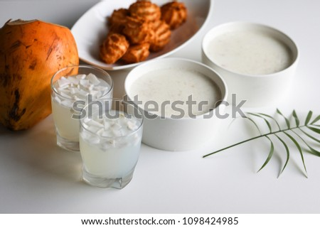 Delicious Tender coconut pudding (dessert) with fresh tender malai juice and coconut macaroons served on white wooden table