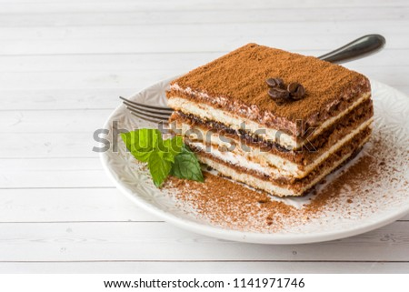 Delicious Tiramisu cake with coffee beans and fresh mint on a plate on a light background. Photo stock ©