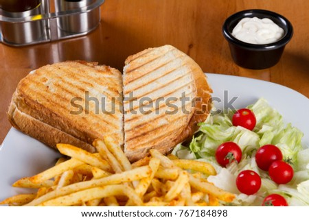 Delicious toasted bread sandwich ingredients ham, cheddar cheese, turkey ham, pork bacon, mushroom, pickles, sliced tomato and hot chili sauce serving with lettuce and golden fried french fries.