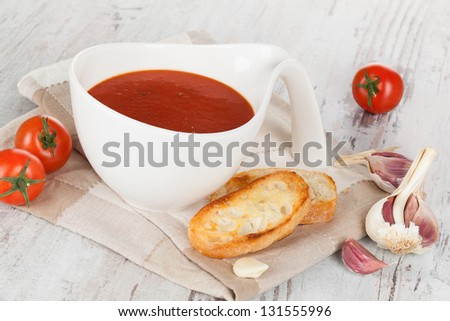 Delicious tomato soup in white bowl with fresh tomatoes, toasted baguette and garlic. Culinary appetizer soup concept.