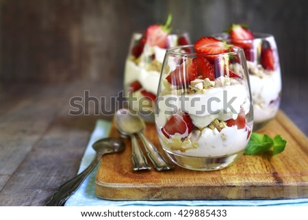 Delicious traditional english dessert eton mess with strawberry on a wooden background. #429885433