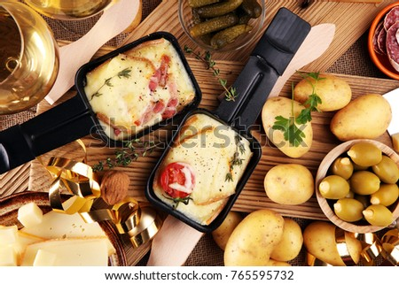 Delicious traditional Swiss melted raclette cheese on diced boiled or baked potato served in individual skillets.