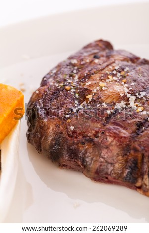 Delicious trimmed lean portion of thick grilled beef steak with seasoning served on a white plate, close up with shallow dof #262069289
