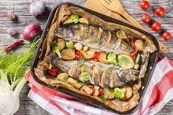 delicious trout fish baked with potatoes, broccoli, lemon, tomatoes and spices in baking dish on a wooden background, top view