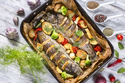 delicious trout fishes baked with potatoes, broccoli, lemon, tomatoes and spices in baking dish on a wooden background, view from above
