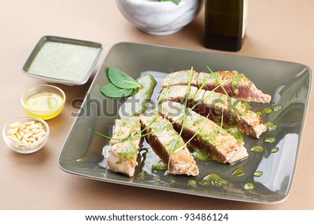 Delicious tuna steak with mint sauce. Sliced and decorated with chive and mint leafs. Served in a trendy green dishware