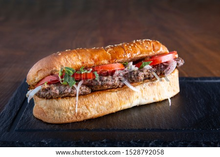 Delicious Turkish Meatballs Sandwich, Kofte Ekmek. Ingredients with bread crumbs, butter, sliced onion, parsley, tomato, pickles and seasoning spices. Hamburger serving on wood table background.