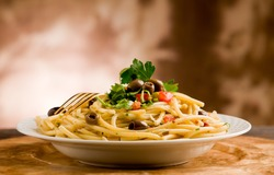 delicious vegetarian dish of pasta with olives and parsley on wooden table