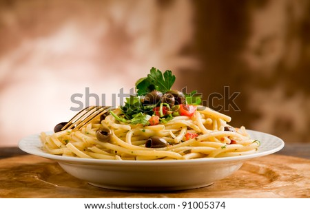delicious vegetarian dish of pasta with olives and parsley on wooden table #91005374