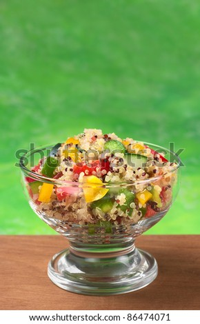 Delicious vegetarian quinoa salad with bell pepper, cucumber and tomatoes (Selective Focus, Focus on the salad in the front)