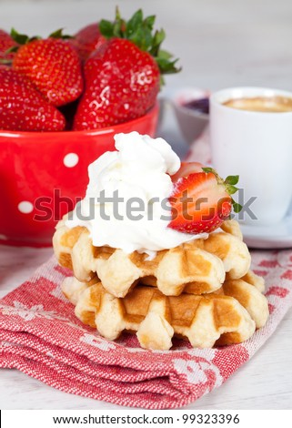 Delicious waffle with whipped cream and strawberries