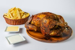 Delicious whole grilled chicken with french fries and creams on wooden plate. Peruvian food