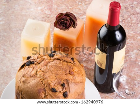 Delicious whole panettone, Christmas cake with glass, bottle of wine, candles, dried red rose set on marble table.