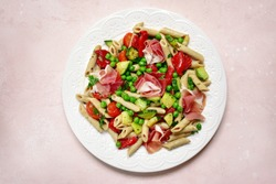 Delicious whole wheat pasta penne with vegetables ( tomato, zucchini, grilled bell pepper, green pea ) and prosciutto on a white plate over slate, stone or concrete background.Top view with copy space