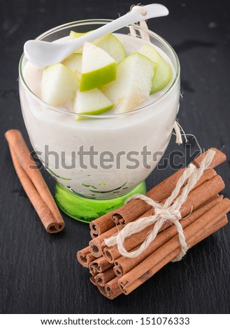 Delicious yogurt in glass with apple and cinnamon on stone table