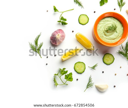 Delicious yogurt sauce in bowl with ingredients on white background
