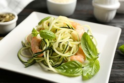 Delicious zucchini pasta with shrimps and basil on black wooden table, closeup