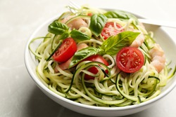 Delicious zucchini pasta with shrimps, cherry tomatoes  and basil in bowl on light grey table, closeup