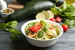 Delicious zucchini pasta with shrimps, cherry tomatoes and basil on grey wooden table