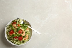 Delicious zucchini pasta with shrimps, cherry tomatoes  and basil on light grey table, top view. Space for text