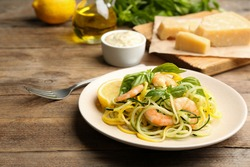 Delicious zucchini pasta with shrimps, lemon and basil on wooden table