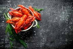 Deliciously cooked red crayfish in a bowl with dill. On dark rustic background