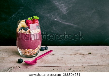 Deliciously sweet acai fruit dessert with pieces of banana, strawberry and blueberry with oats next to spoon on wooden table with copy space
