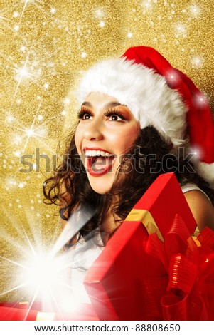Delighted, beautiful, happy woman with gift box in santa claus hat