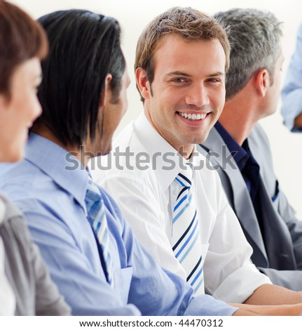 Delighted businessman looking at the camera in a meeting with his team