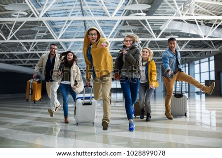 Delighted companions running to airport registration desk. Some of them holding bags in hands