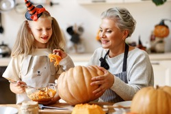 Delighted elderly woman and girl smiling and removing insides of ripe pumpkin while carving jack o lantern for Halloween celebration at home