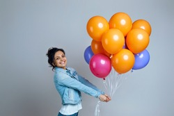 delighted girl in denim posing with bright colorful air balloons isolated on gray background. Beautiful happy young woman on a birthday party.