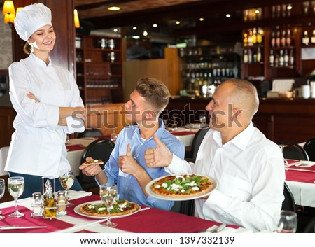 Delighted guests lauding young female chef while enjoying pizza in cozy restaurant #1397332139