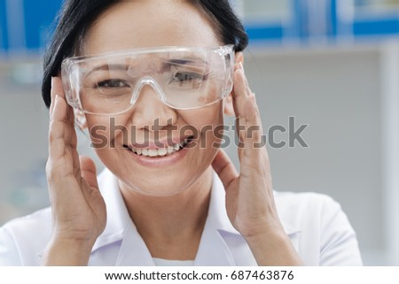 Delighted laboratory scientist fixing her protective glasses