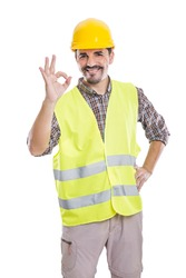 Delighted male builder in yellow helmet and reflective vest standing with hand on waist on white background and showing okay sign while looking at camera