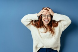 Delighted or overjoyed young redhead woman holding her hands to her forehead with a beaming smile of pleasure on a blue studio background with copy space