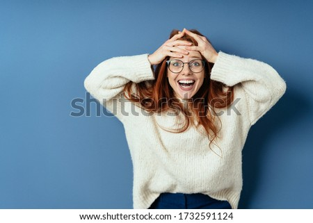 Delighted or overjoyed young redhead woman holding her hands to her forehead with a beaming smile of pleasure on a blue studio background with copy space Photo stock ©