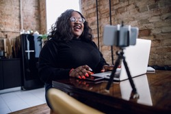 Delighted plus size lady in front of a laptop and a smartphone on tripod laughing