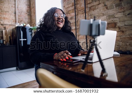Delighted plus size lady in front of a laptop and a smartphone on tripod laughing ストックフォト ©