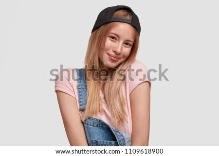 Delighted pretty female in stylish cap and denim overalls, has happy shy expression, meets with handsome youngster, has charming smile on face, poses against white background. Teenagers and lifestyle