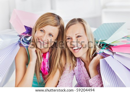 Delighted two women holding shopping bags smiling at the camera at home