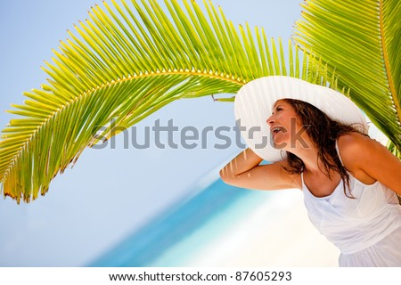 Delighted woman at the beach enjoying her holidays and smiling
